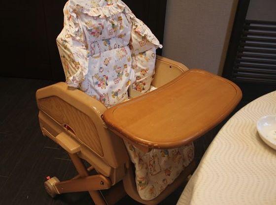 優しい木製のベビーコットとハイチェアにはテーブルや安全ベルトが付いています。